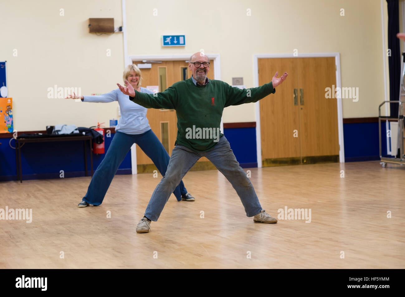 Two Middle aged people - man and woman,  taking part in a Tai Chi exercise workshop lesson class at Tregaron Memorial - Stock Image