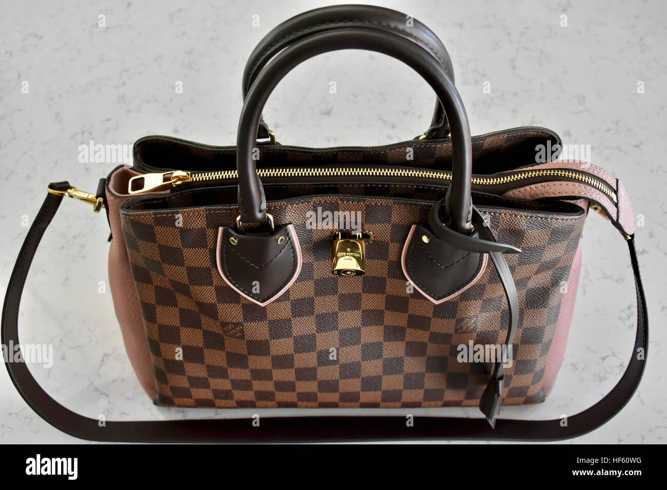 bf80ca493b38 A Louis Vuitton handbag displayed on a white carrera marble background