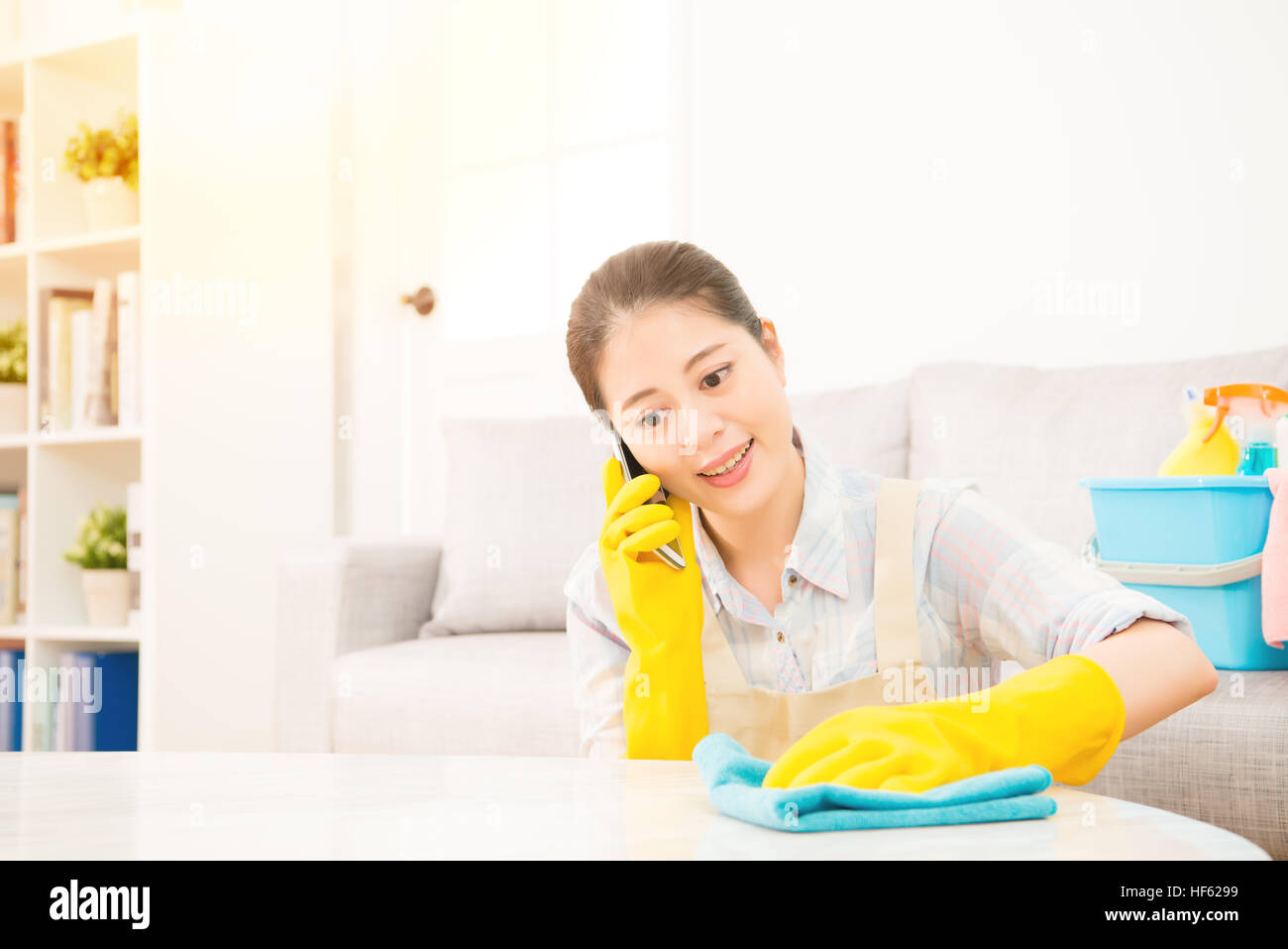 Smiling girl cleaning with glove and speaking on the phone. Pretty smiling young mixed race Asian girl Stock Photo