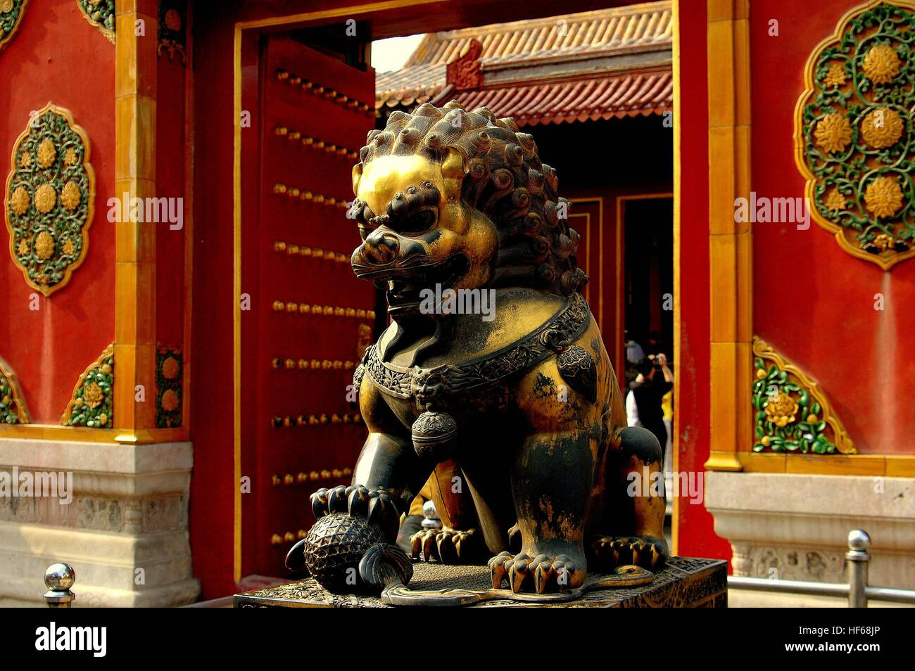 Beijing, China - May 2, 2005:  A gilded bronze lion guards an entry gate at the Chang Chung Palace in the Forbidden - Stock Image