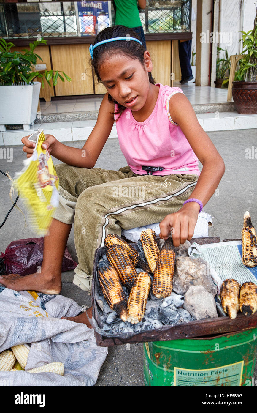 A young Filipino girl in Bogo City, Cebu Island in the Philippines roasts ears of corn over charcoal at her sidewalk - Stock Image