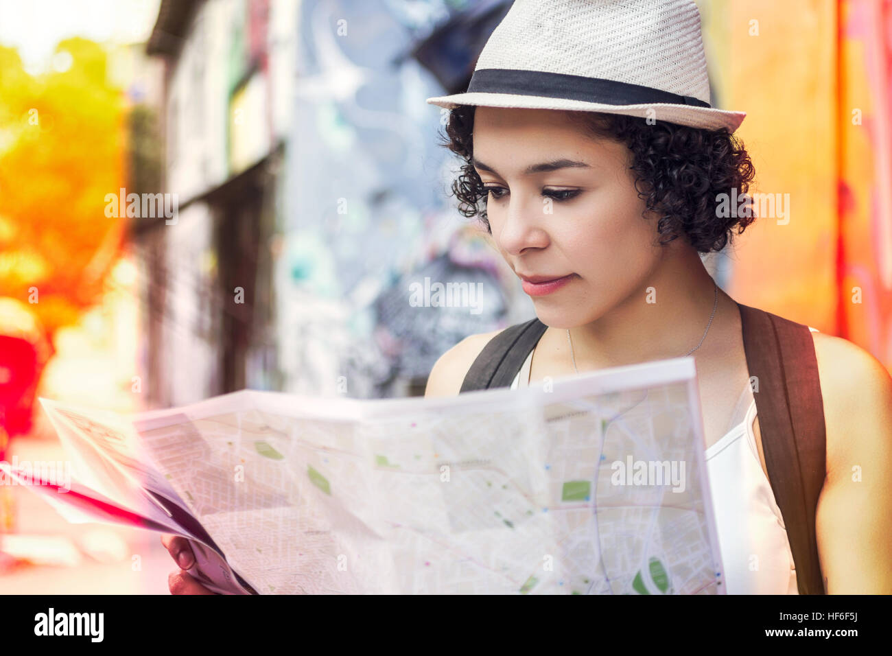 Young traveller looking at street map with touristic information. Blurred background, color filter. - Stock Image