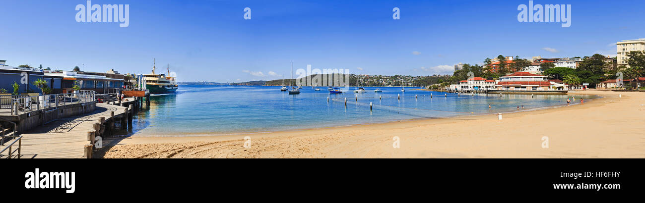 Relaxing sunbathing people at Manly beach protected with shark nets in bay between manly wharf ferry terminal and - Stock Image