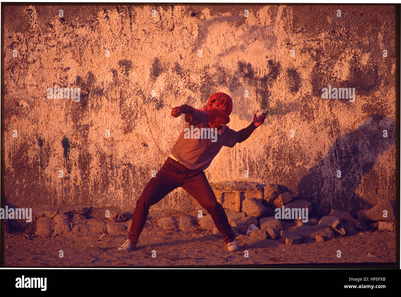 A PLO fighter throws rocks at Israeli Army soldiers during the first Intifada. - Stock Image