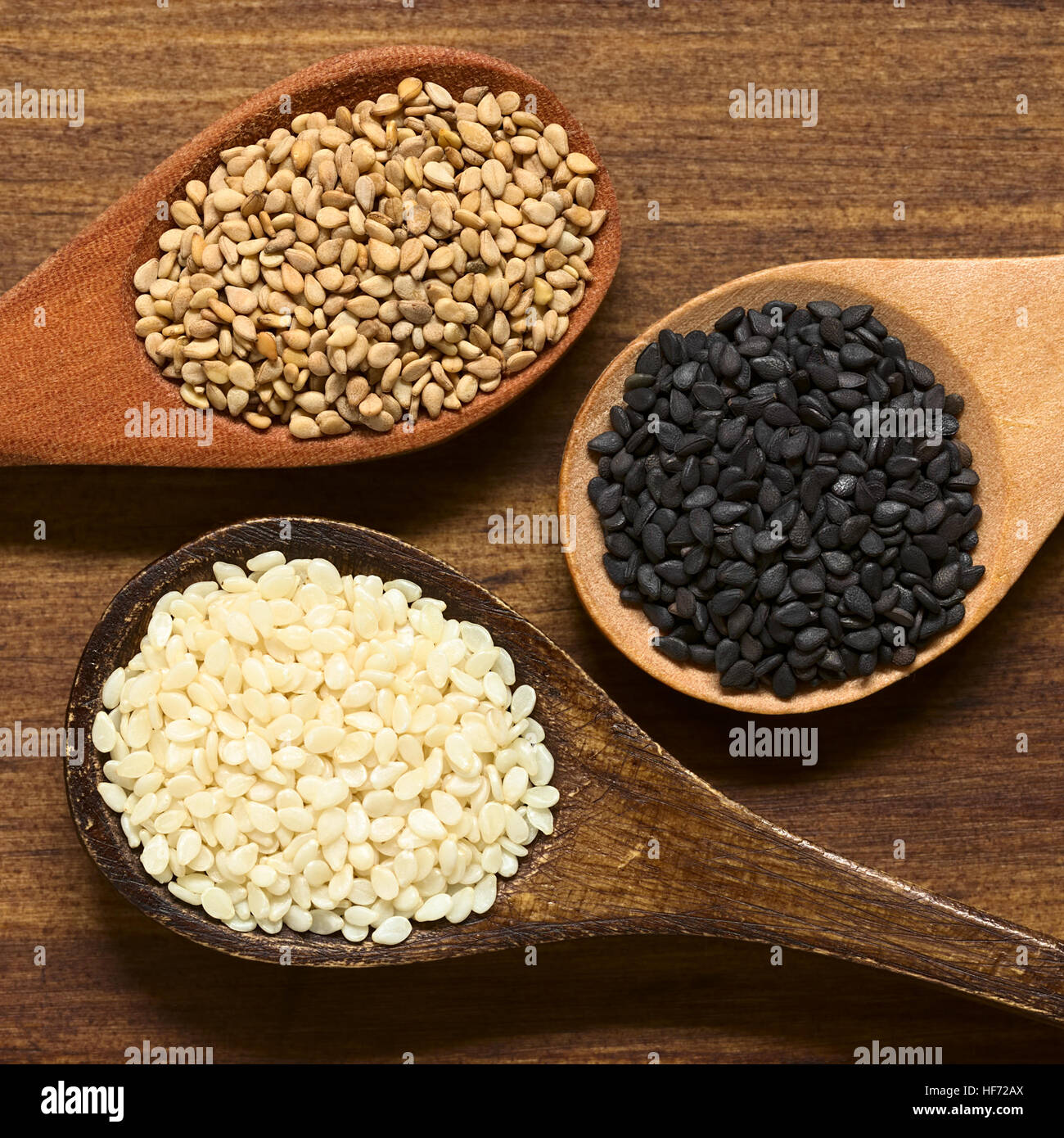 Black, white and roasted sesame seeds on small wooden spoons, photographed overhead on wood with natural light (Selective - Stock Image