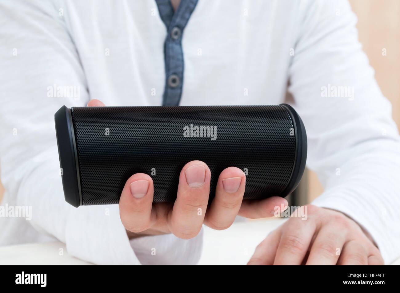 Man shows Modern wireless audio device. - Stock Image