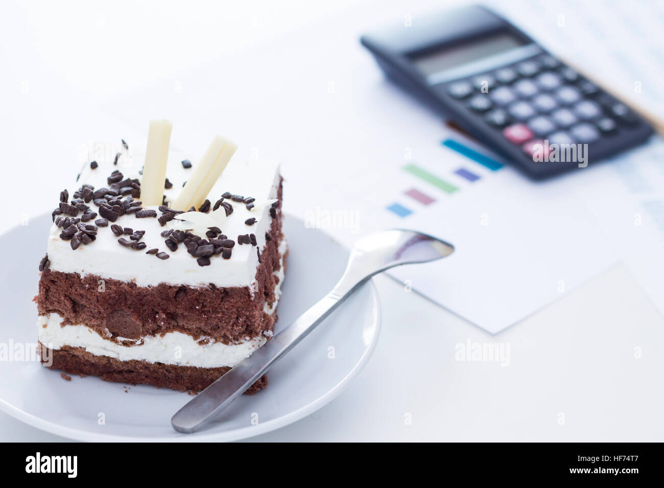 Time for something sweet. Sponge cake with chocolate on the desk. - Stock Image