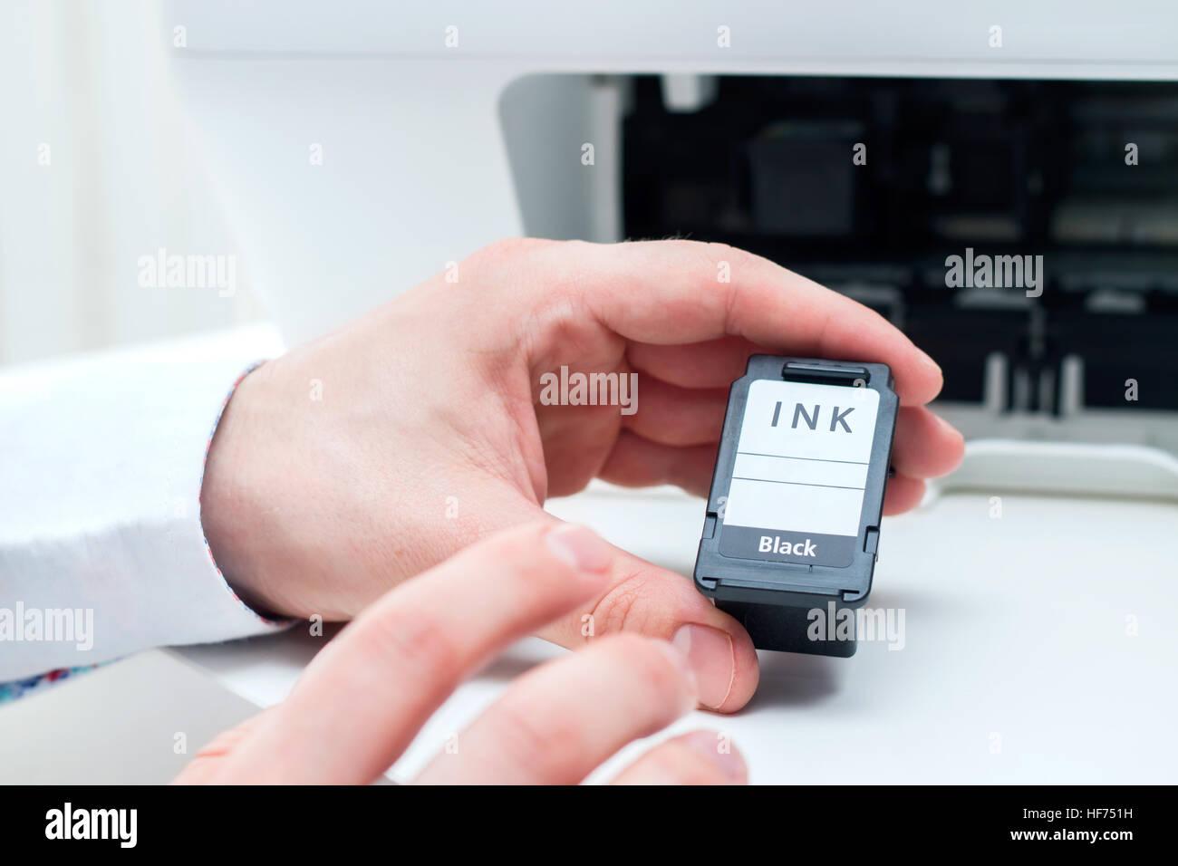 Man replace black ink cartridge in white printer - Stock Image
