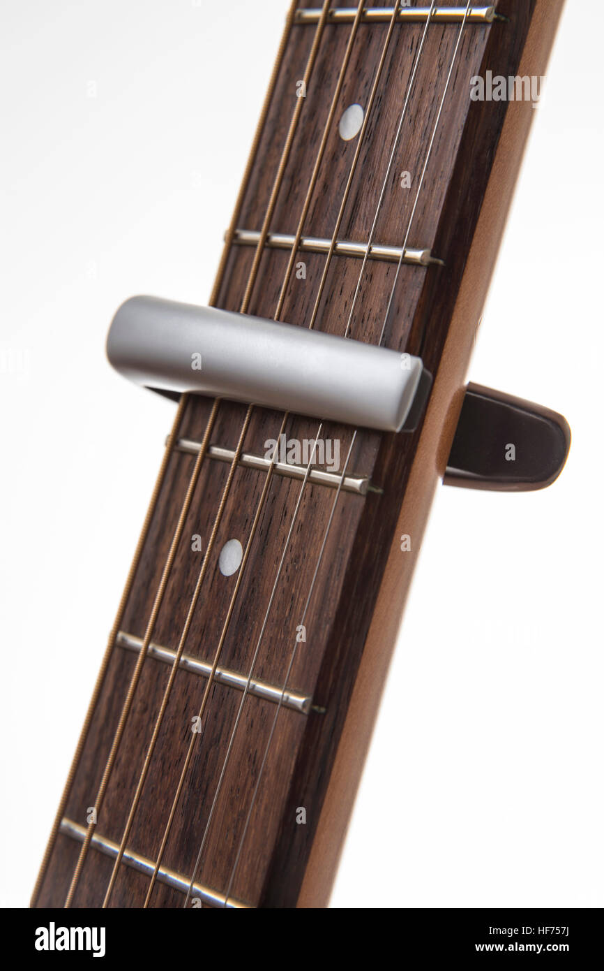 G Clamp type guitar capo positioned between the frets on a rosewood neck, - Stock Image