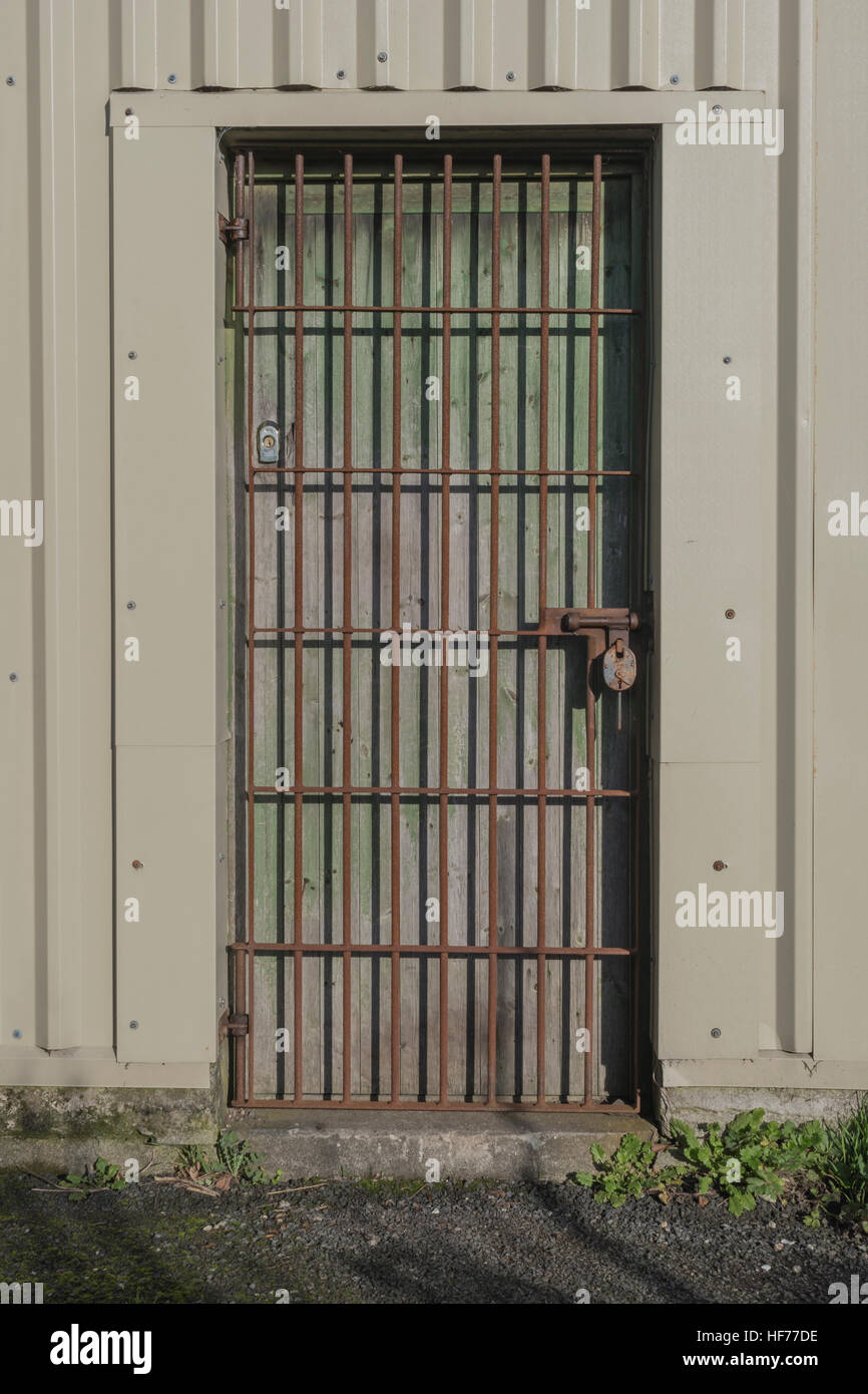Security Gated And Padlocked Doorway Of A Workshop On An Industrial Estate.  Security Gate Metaphor