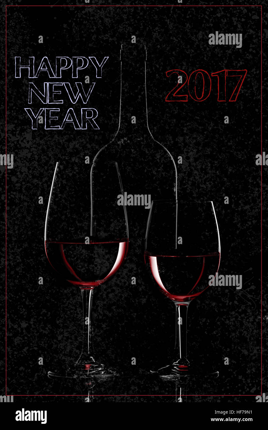 happy new year 2017 greetings with red wine bottle and two wine glasses on black background
