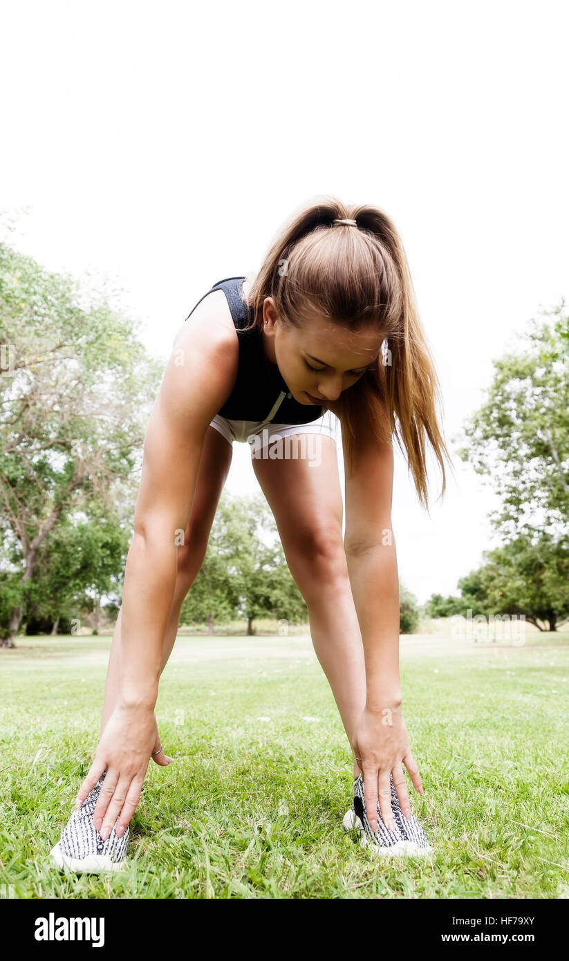 Caucasian Teen Woman Stretching Outdoors On Green Grass White Shorts Hands To Toes Stock Photo