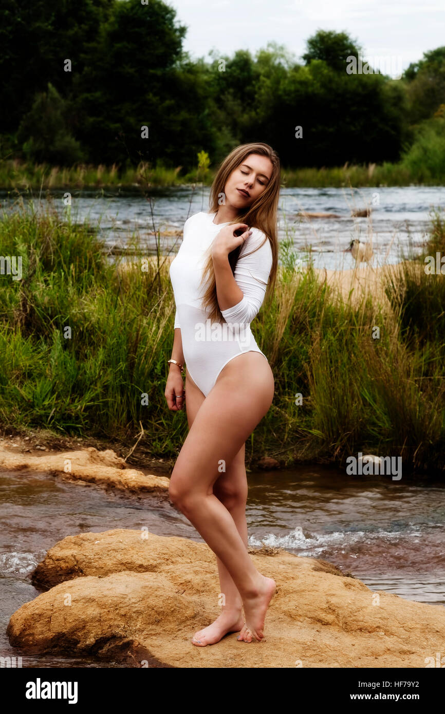 Caucasian Teen Girl At River In White Leotards With Eyes Closed Stock Photo