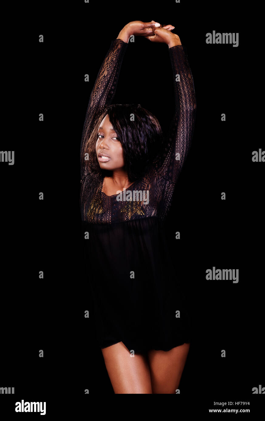 Attractive African American Woman In Black Nightie On Dark Background Standing With Arms Up Stock Photo