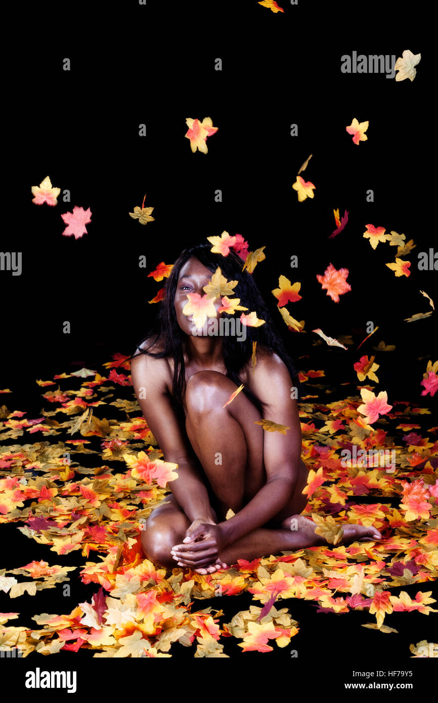 Attractive African American Woman Sitting Implied Nude Among Silk Autumn Leaves In Studio Throwing Them Stock Photo