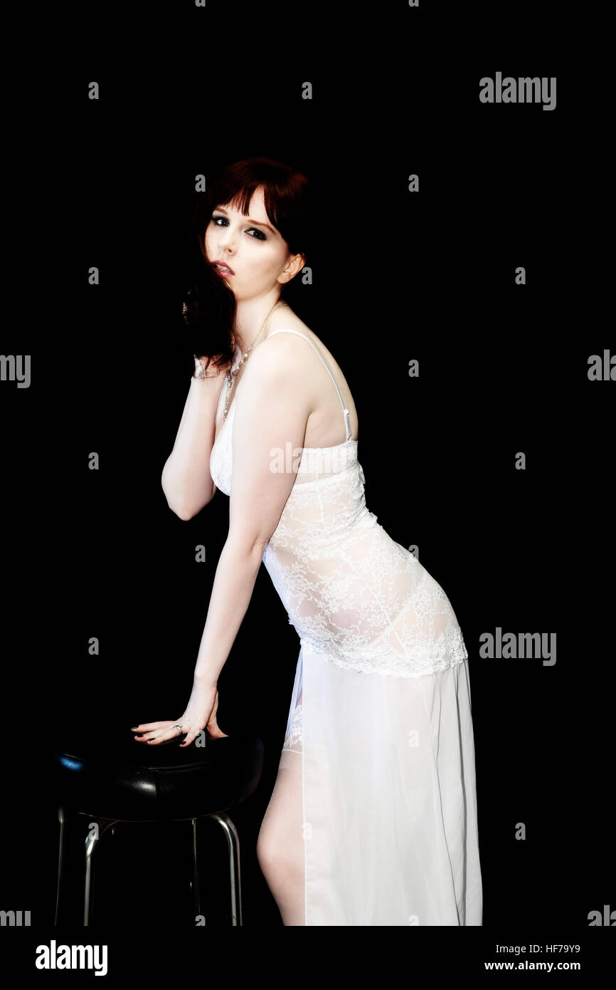 Caucasian Woman Standing In White Lingerie Against Dark Background Leaning On Stool Stock Photo