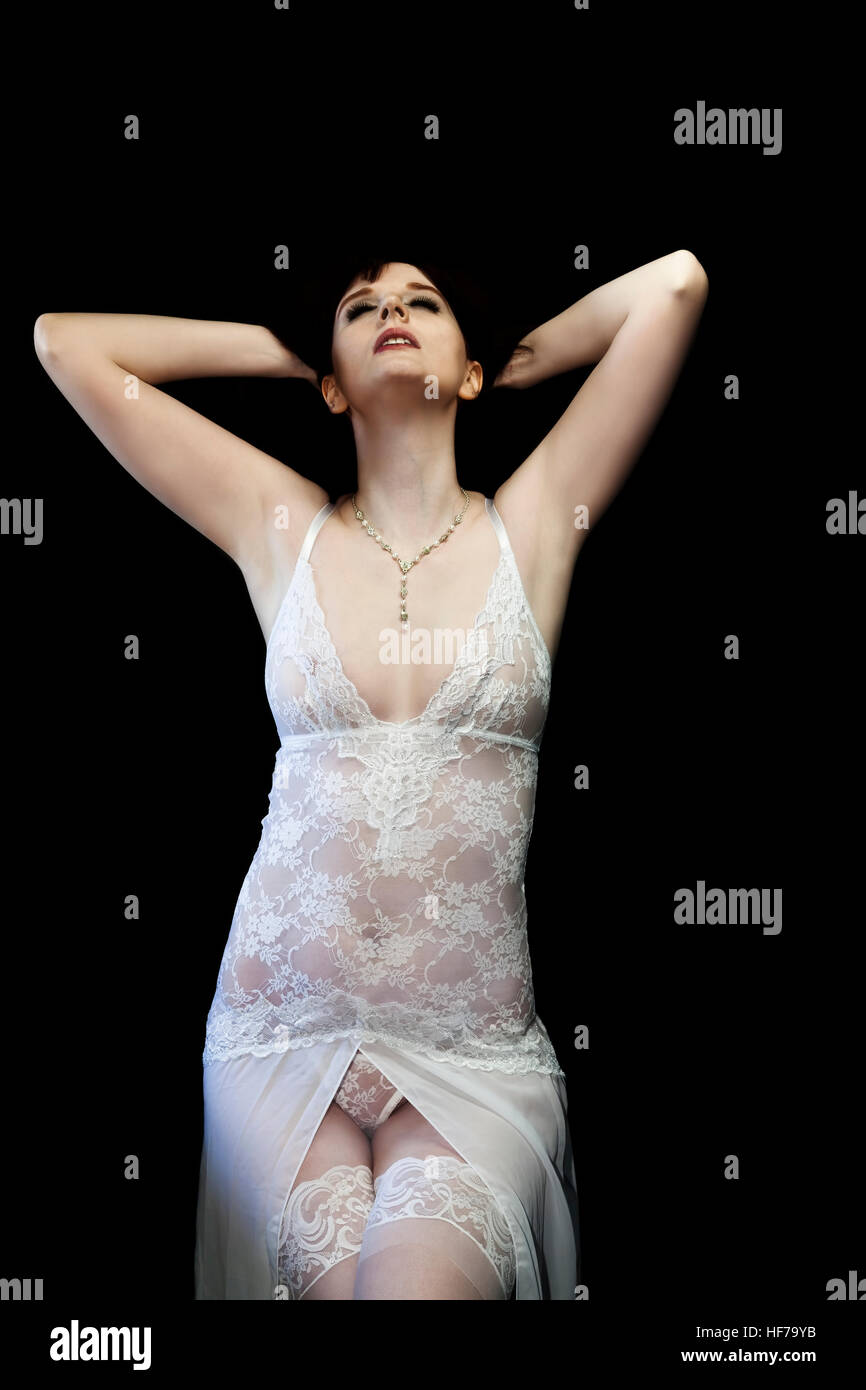Caucasian Woman Arms Behind Head Looking Up With Closed Eyes Wearing White Lace Lingerie Stock Photo