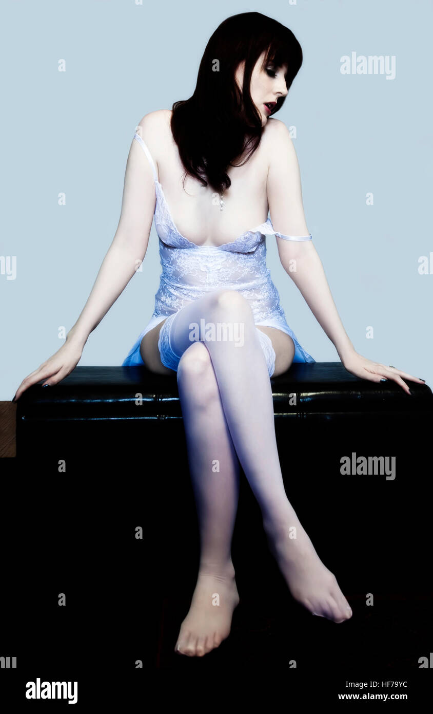 Caucasian Woman In White Lace Lingerie Sitting Stockings Showing Cleavage Stock Photo