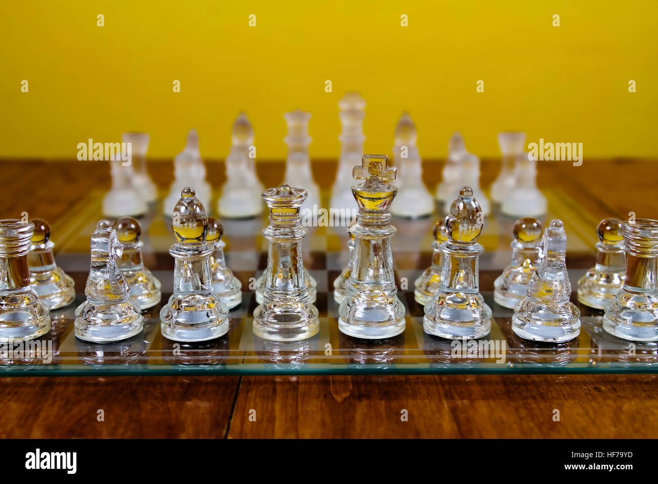 Glass Chess Pieces Set Up On Board In Starting Position Sitting On Wood Table With Yellow Wall Stock Photo