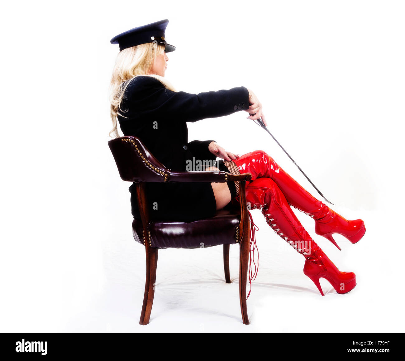 Older Caucasian Woman Sitting In Chair With Red Boots Jacket And Hat With Riding Crop Stock Photo