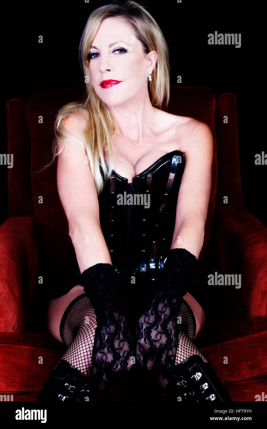 77590ebe0a7 Older Caucasian Blond Woman Sitting On Red Chair In Black Corset Fishnet  Stockings Lace Gloves Showing