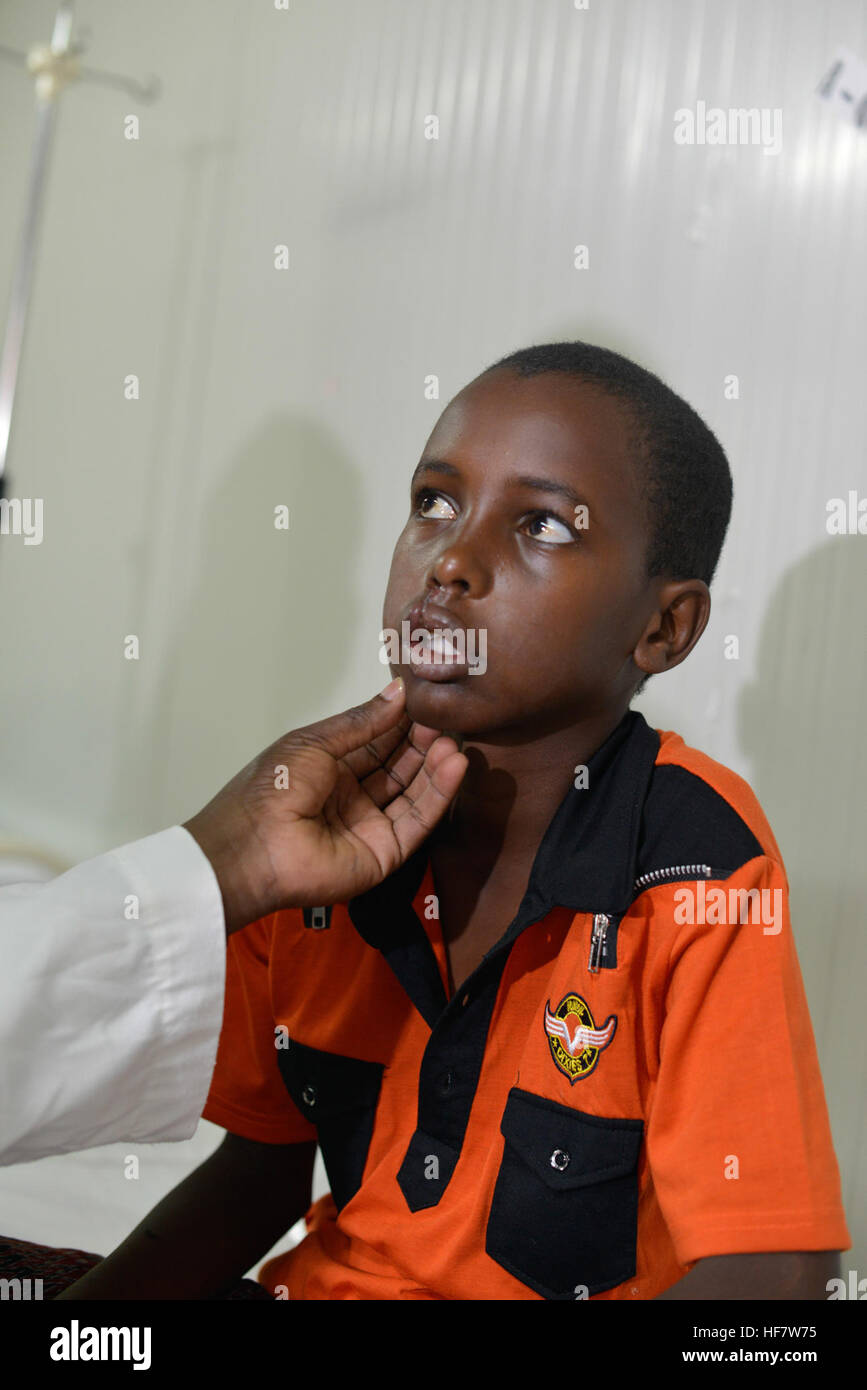 An AMISOM paramedic checks a 12-year-old boy after his