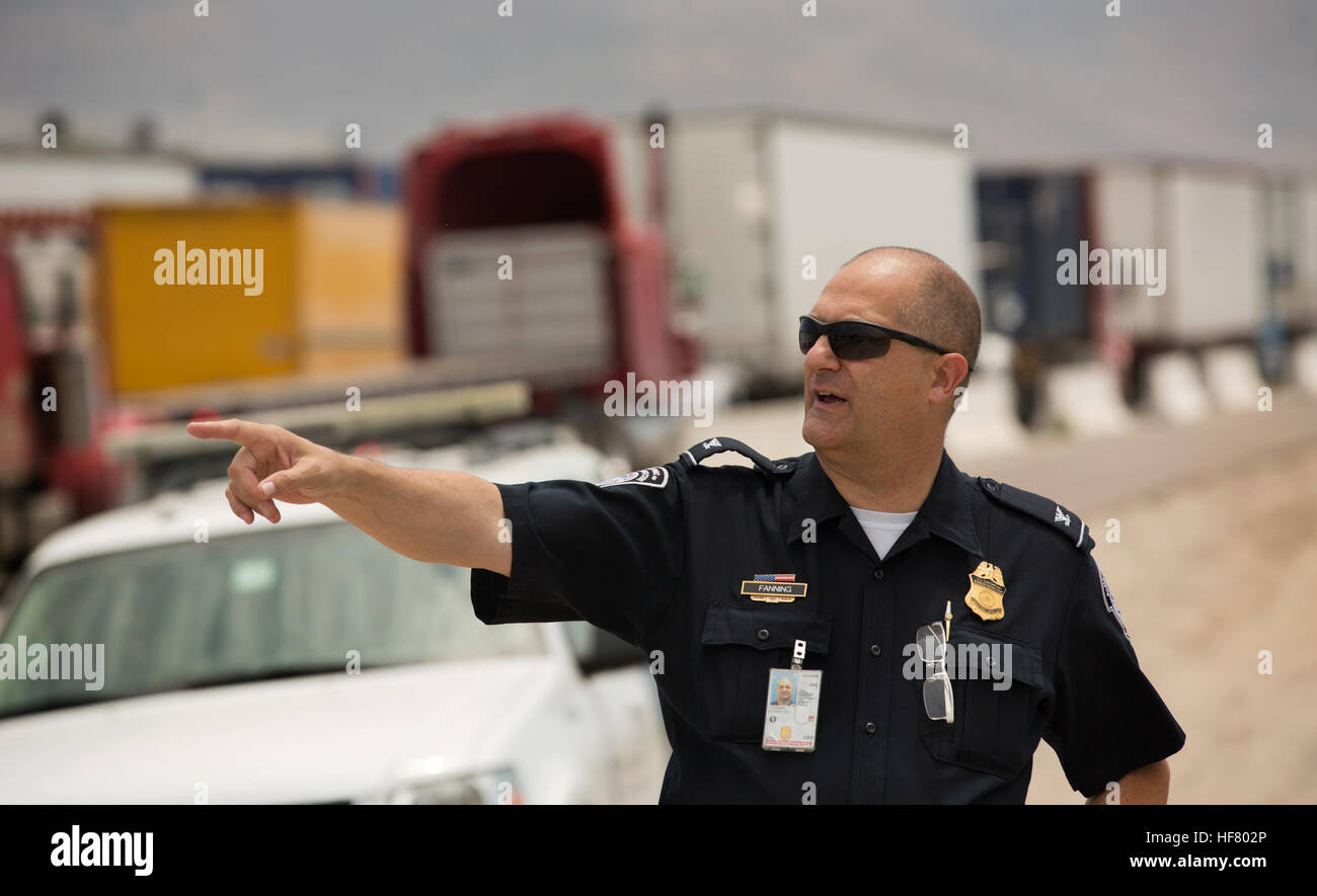 U.S. Customs and Border Protection officer Larry Fanning points towards a line of trucks awaiting entry inspections - Stock Image