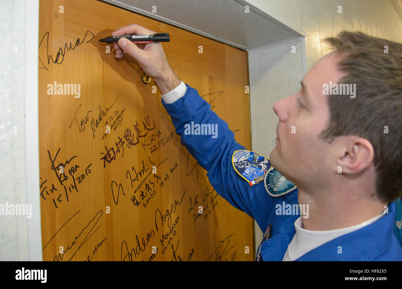 Expedition 50 ESA astronaut Thomas Pesquet performs the traditional door signing at the Cosmonaut Hotel prior to - Stock Image