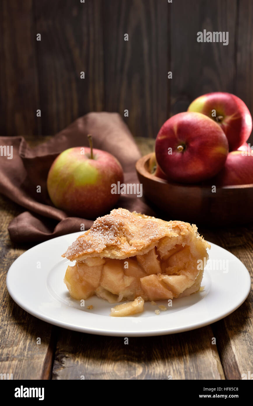 Piece of apple pie ad fresh fruits on wooden table - Stock Image