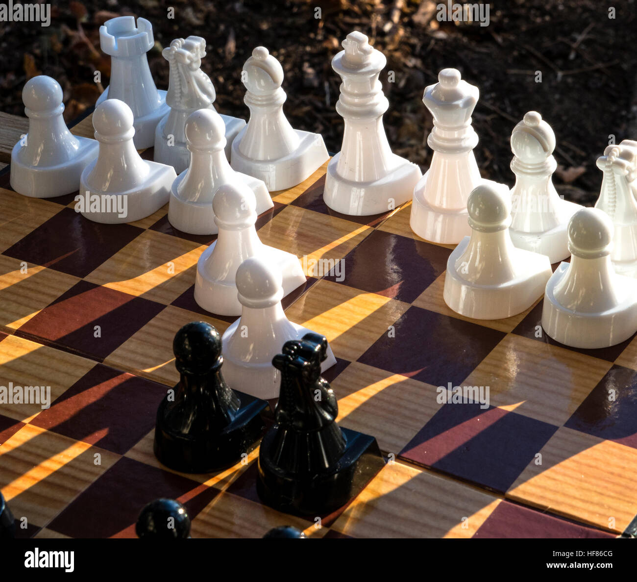 Chess set showing white and black chess pieces on a chess board - Stock Image
