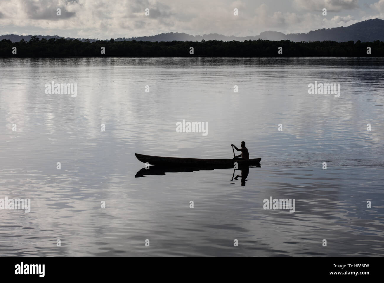 A fisherman paddles his dugout canoe in calm water between remote islands in the Solomon Islands. - Stock Image