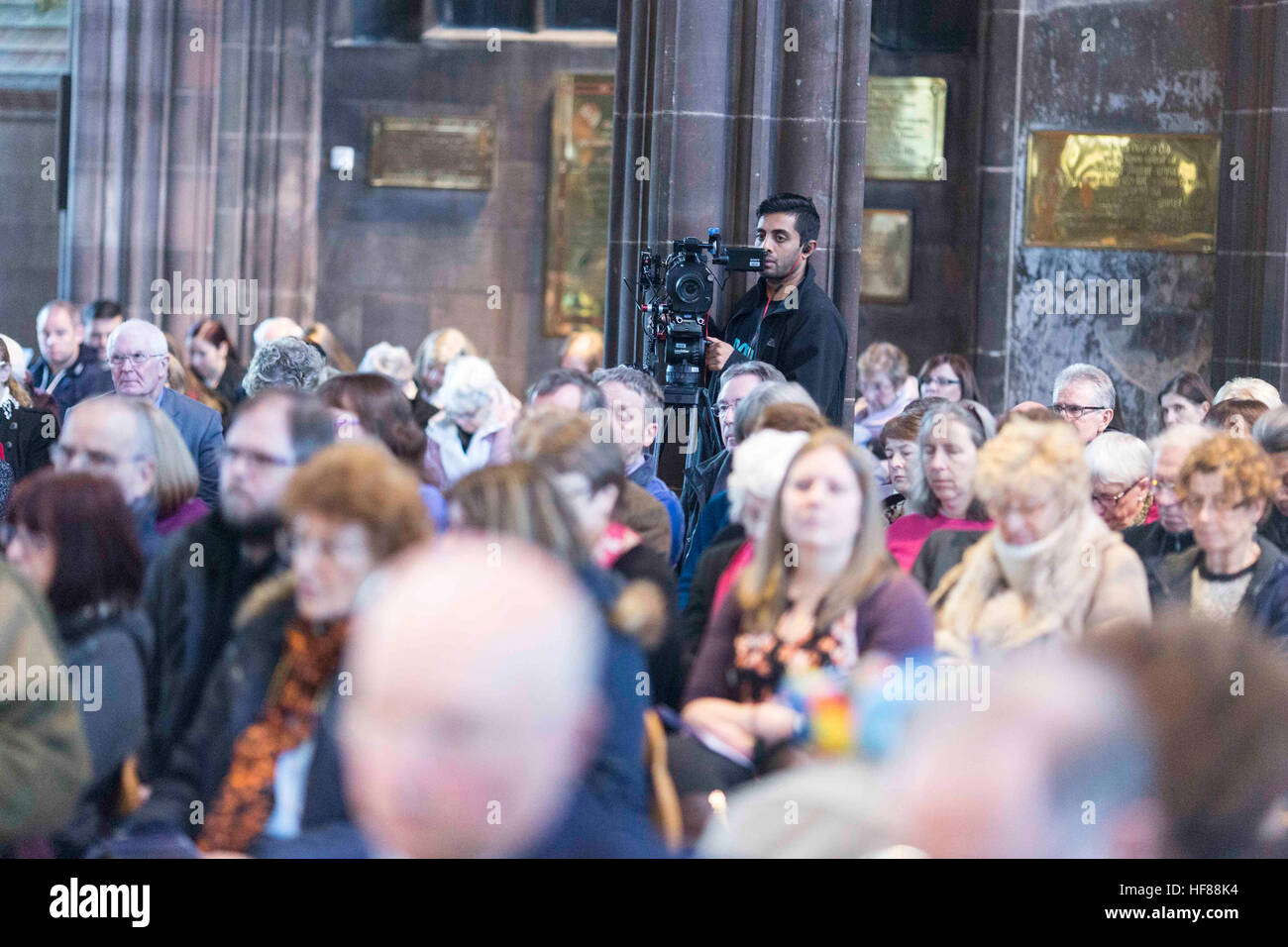 Interior of Manchester Cathedral during a service. A TV camera records the service - Stock Image