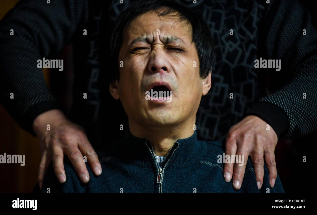 (161228) -- HENGSHUI, Dec. 28, 2016 (Xinhua) -- Wang Mingchen massages for Li Jianguo at Li's home in Taocheng - Stock Image