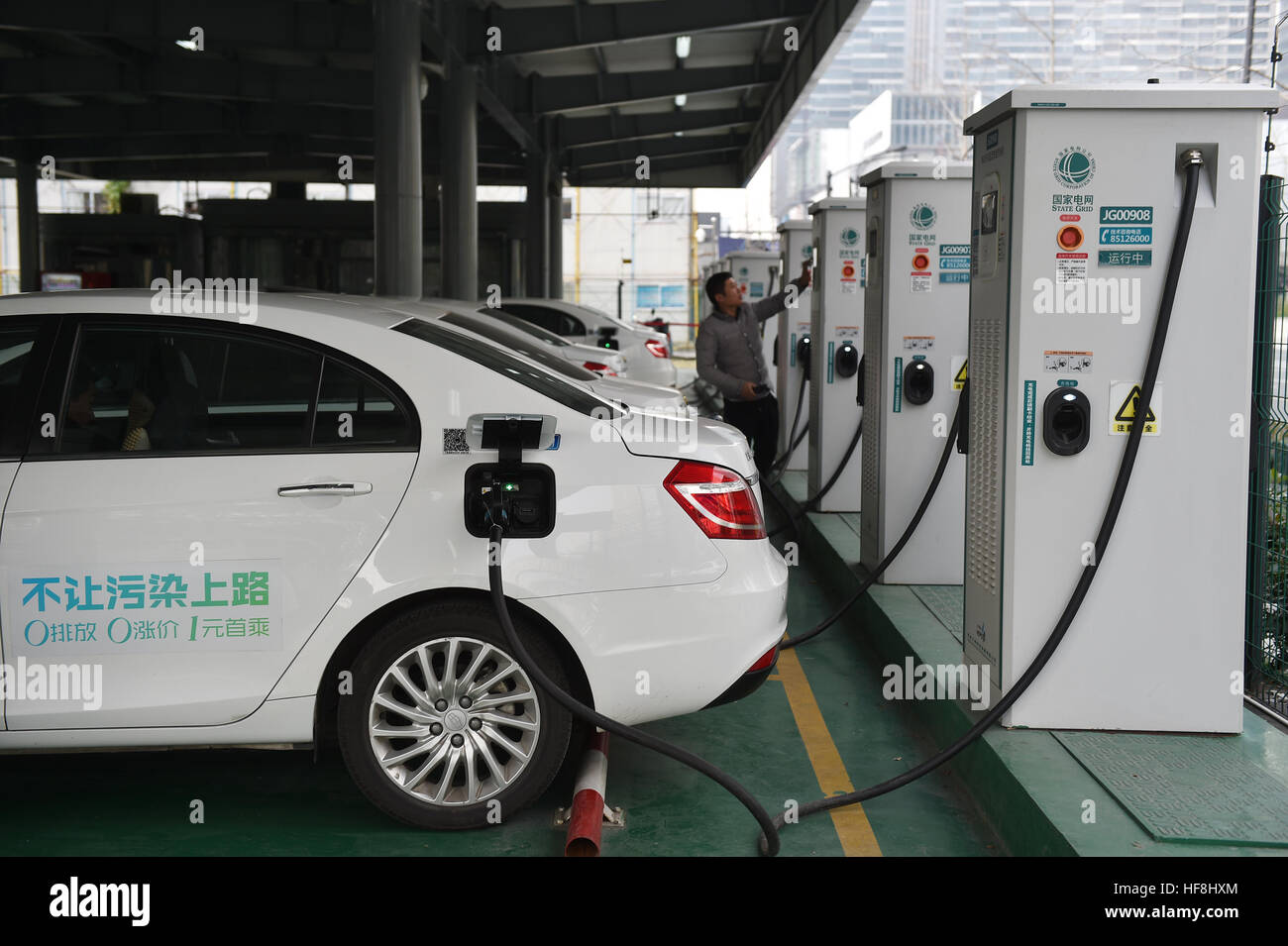 Hangzhou, China's Zhejiang Province. 29th Dec, 2016. A driver charges his electric car at a charging station - Stock Image