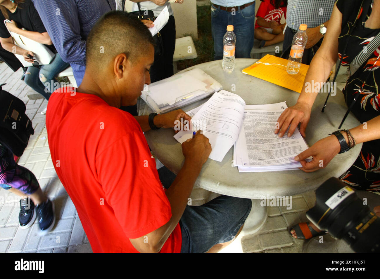 SÃO PAULO, SP - 29.12.2016: ENTREGA DE APARTAMENTOS DA PRIMEIRA PPP - Pictured resident signs the apartment purchase contract. Governor Geraldo Alckmin delivered on the morning of Thursday (29), at Rua São Caetano in downtown São Paulo, 126 apartments of the first Public-Private Partnership (PPP) in the country housing for low-income families. They attended the event Mayor Fernando Haddad and the mayor elected John Doria. (Photo: Aloisio Mauricio/Fotoarena) Stock Photo
