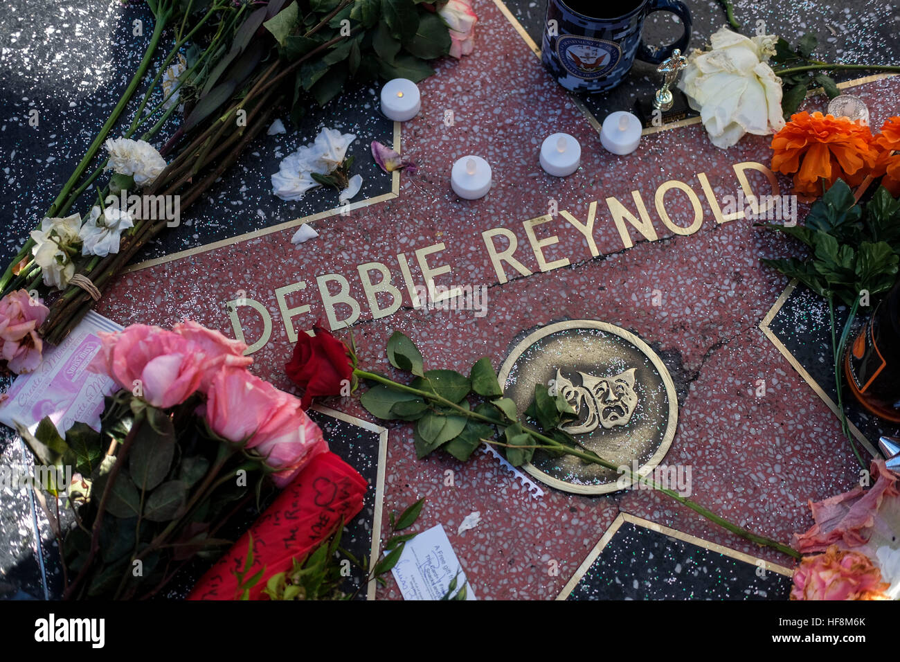 Los Angeles, USA. 29th Dec, 2016. Flowers and candles surround the Hollywood Walk of Fame star of Debbie Reynolds, - Stock Image