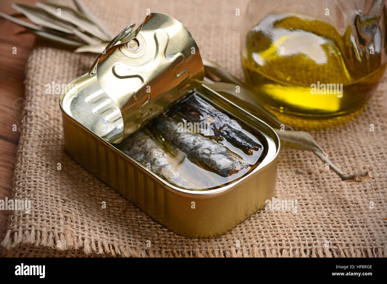 tinned anchovies in oil on the wooden table - Stock Image