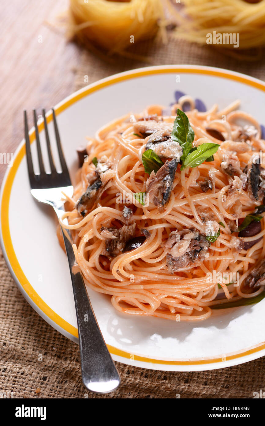 spaghetti and anchovies with ingredients around - Stock Image