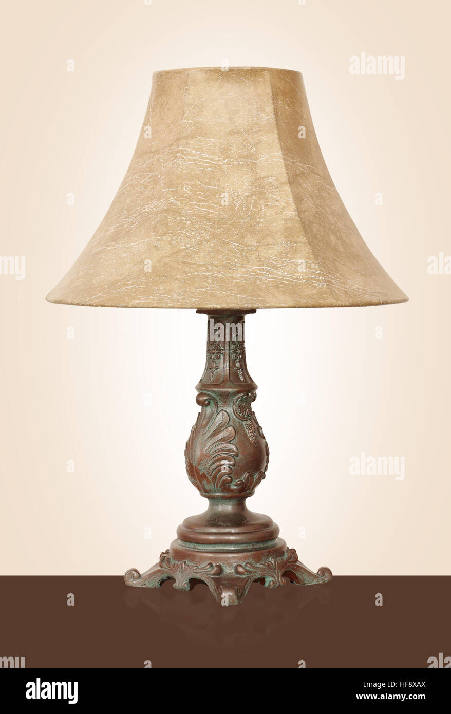 Light fixture - Vintage Desk lamp with the powerful brass basis on a beige background - Stock Image
