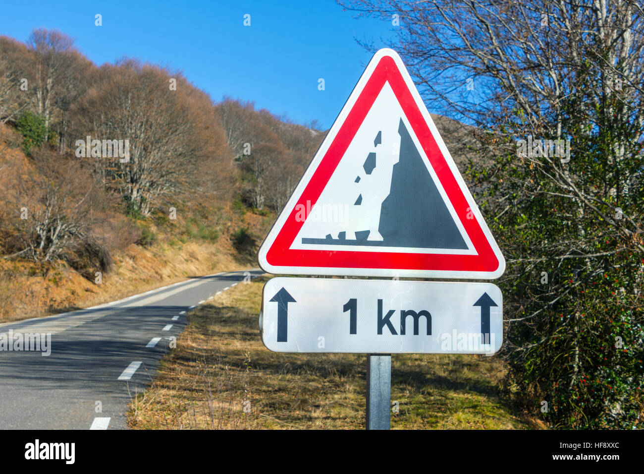 Falling rocks 1km triangular road sign with blue sky - Stock Image