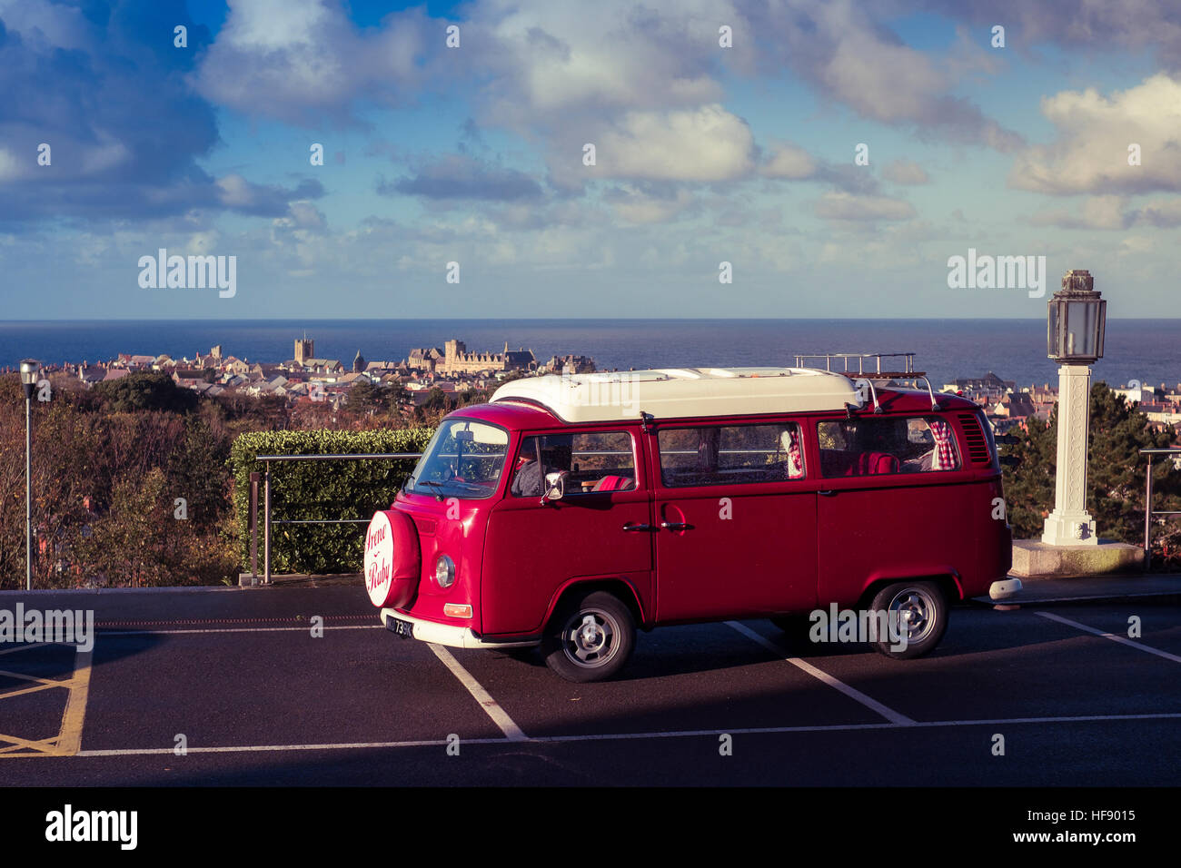 c131120147 A classic Volkswagen VW Type 2 red campervan parked overlooking the town of  Aberystwyth on the west wales coast UK