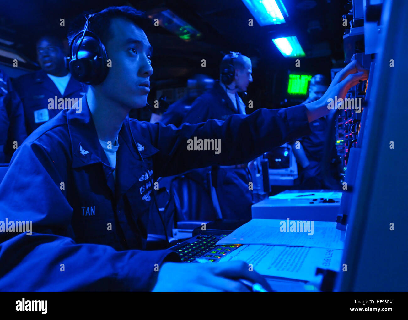 us navy operations specialist 3rd class eric tan stands watch in the combat information center aboard the forward deployed amphibious assault ship uss