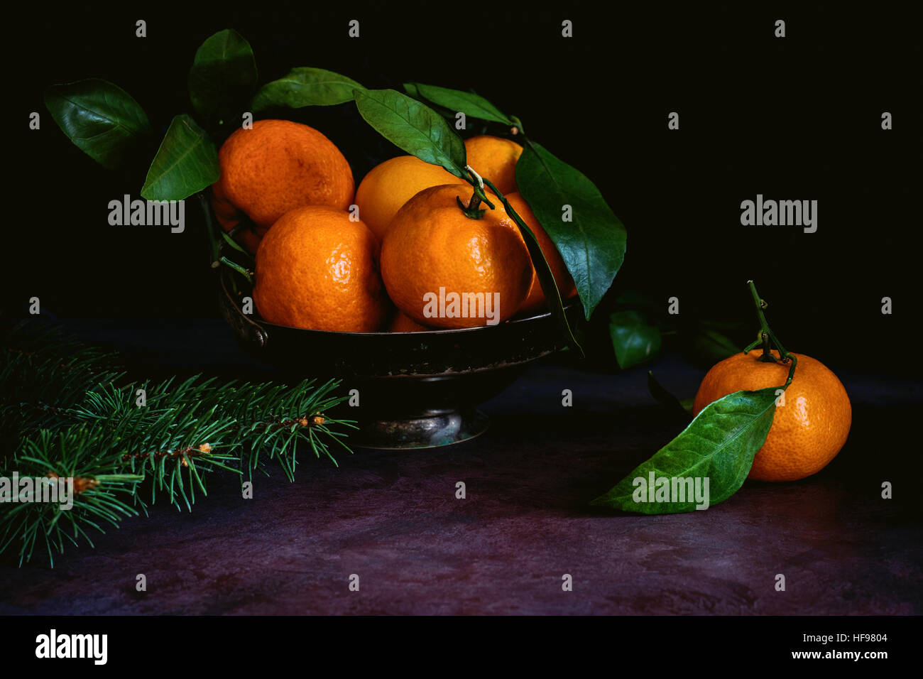 Still life of fresh tangerines with green leaves in vintage metal bowl. Toned image, low key technique (chiaroscuro) - Stock Image