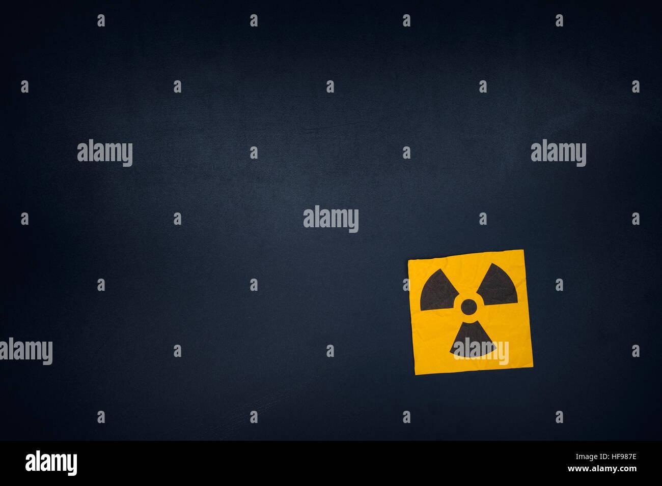 Radiation warning sign on a blackboard. Vignette. - Stock Image