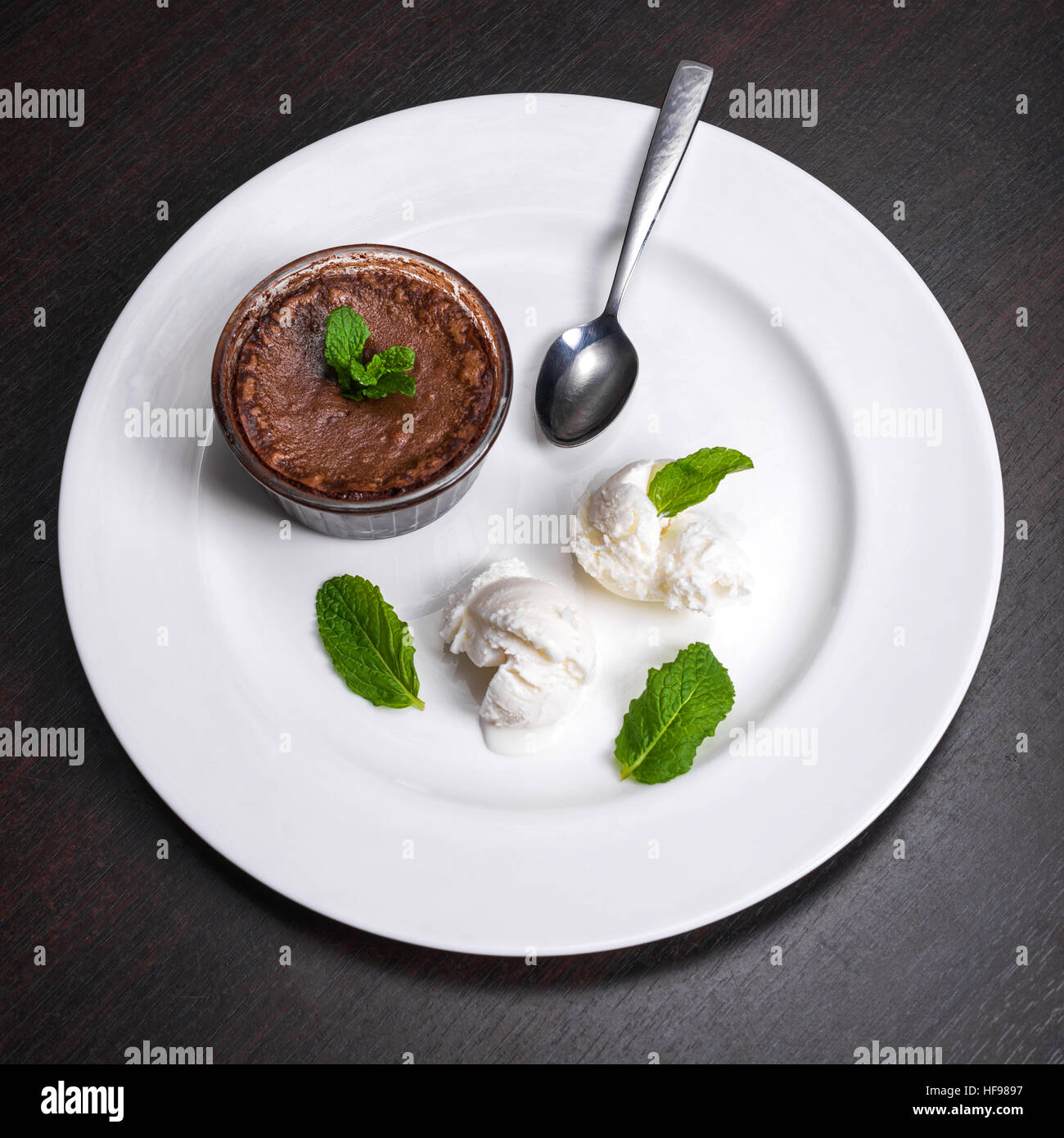 Warm dessert chocolate fondant lava cake served with vanilla ice cream balls and mint on white plate. Famous French Stock Photo