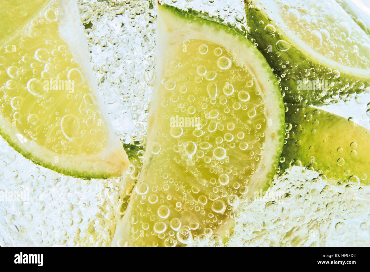 Lime slices in a fizzy drink, close-up Stock Photo