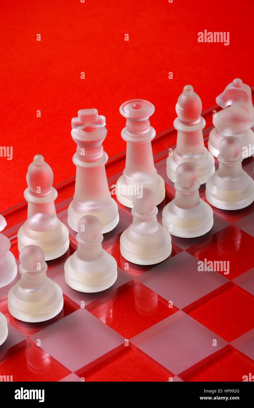 Glass chess on the chessboard - red background - Stock Image