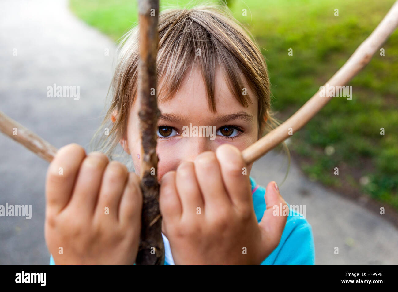 Portrait of a six-year girl with a wooden stick - Stock Image