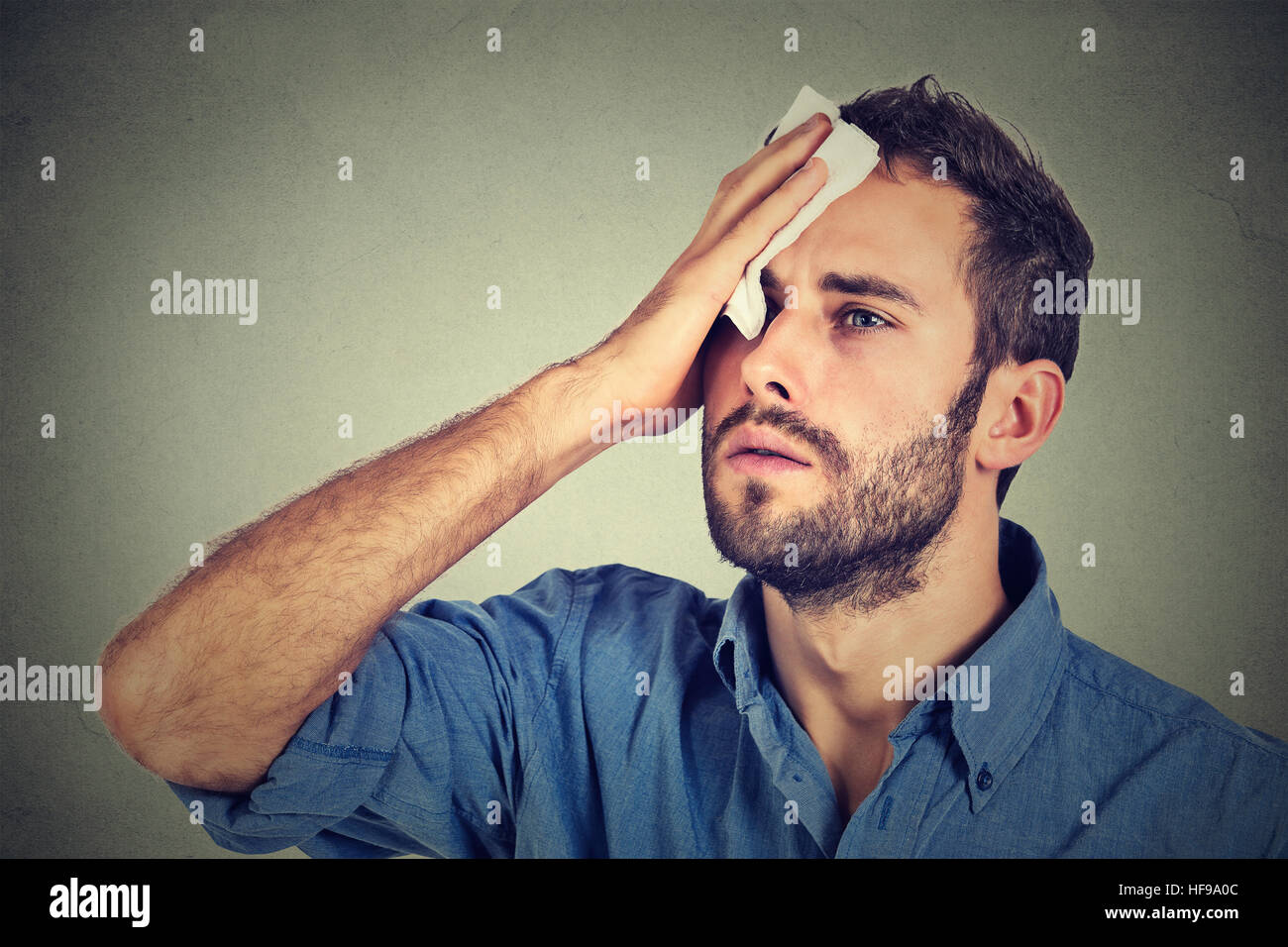 Tired man stressed sweating having fever headache isolated on gray wall background. Worried guy wipes sweat on his - Stock Image