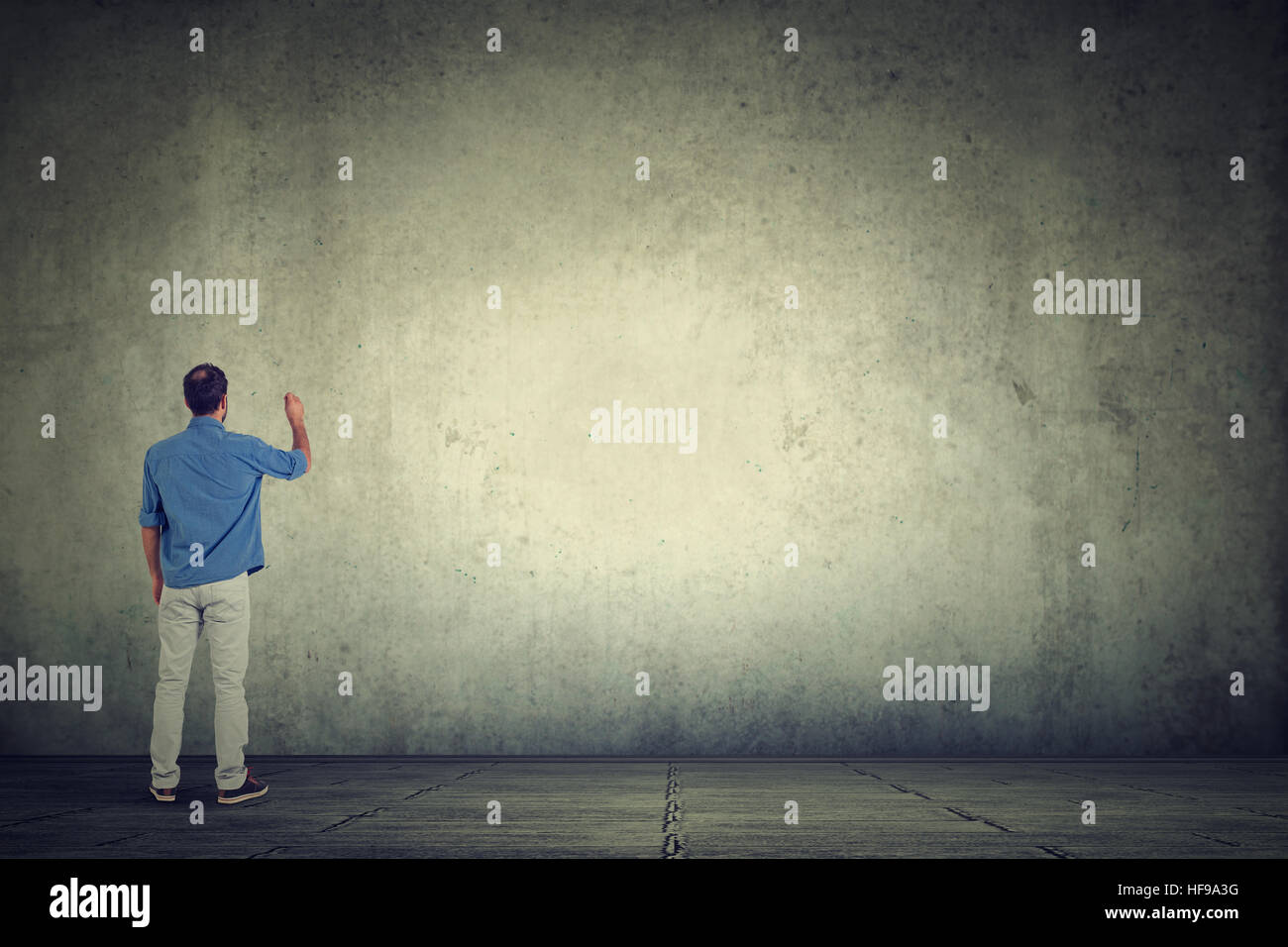 Young student man writing something on a large empty gray wall - Stock Image